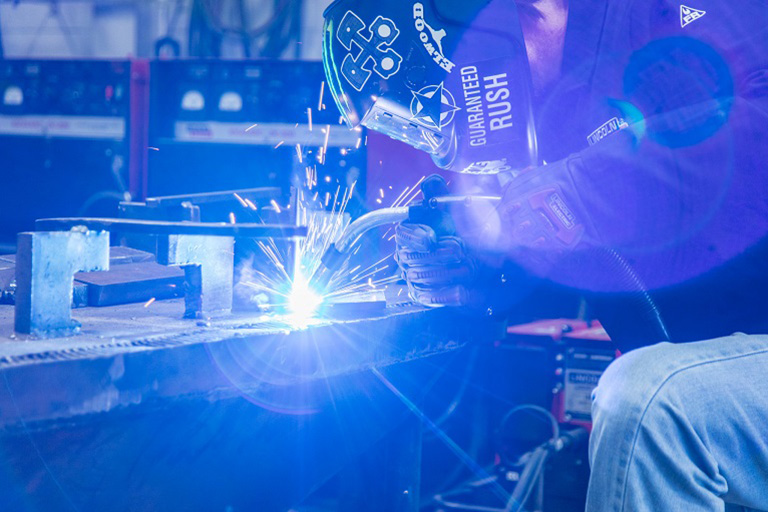 welder welding with helmet and blue sparks