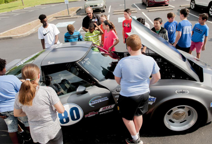 Middle School student gather around a car built by automotive technology students.
