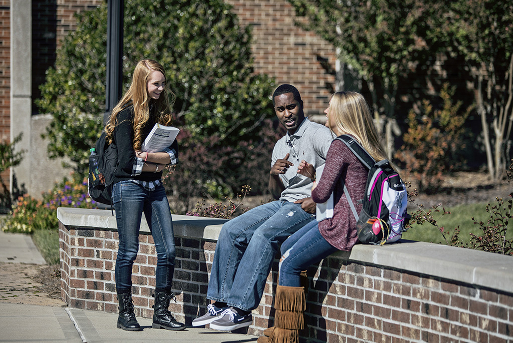 One female student standing talking to a male and female student sitting on a brick wall on campus
