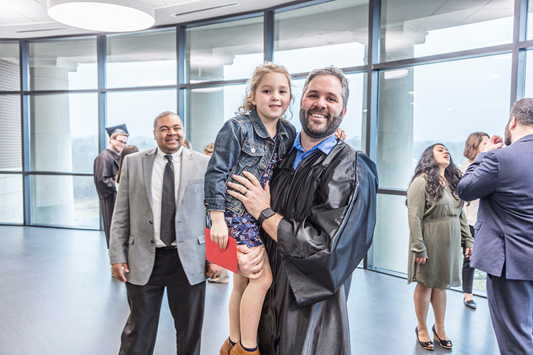 Father graduating, holding daughter in his arms