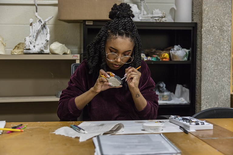 woman of color using art supplies at a table