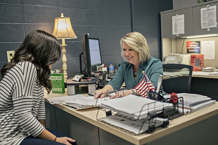 Female student in office speaking with a female financial aid counselor