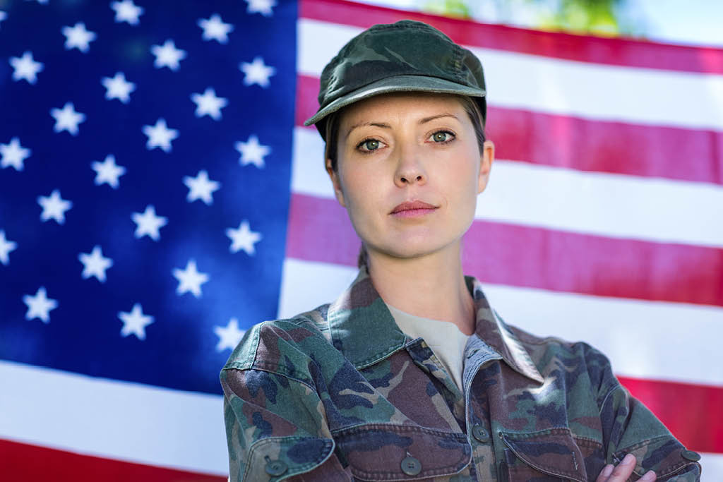 Female soldier standing infront of USA flag.