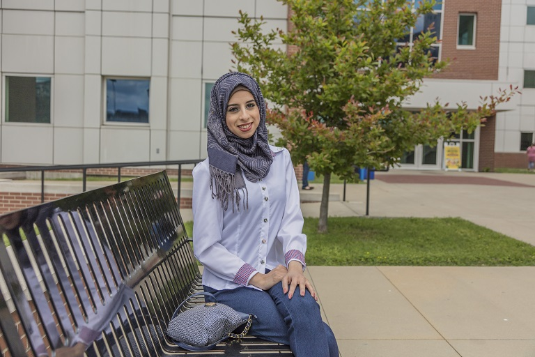 Woman in hijab sitting on bench