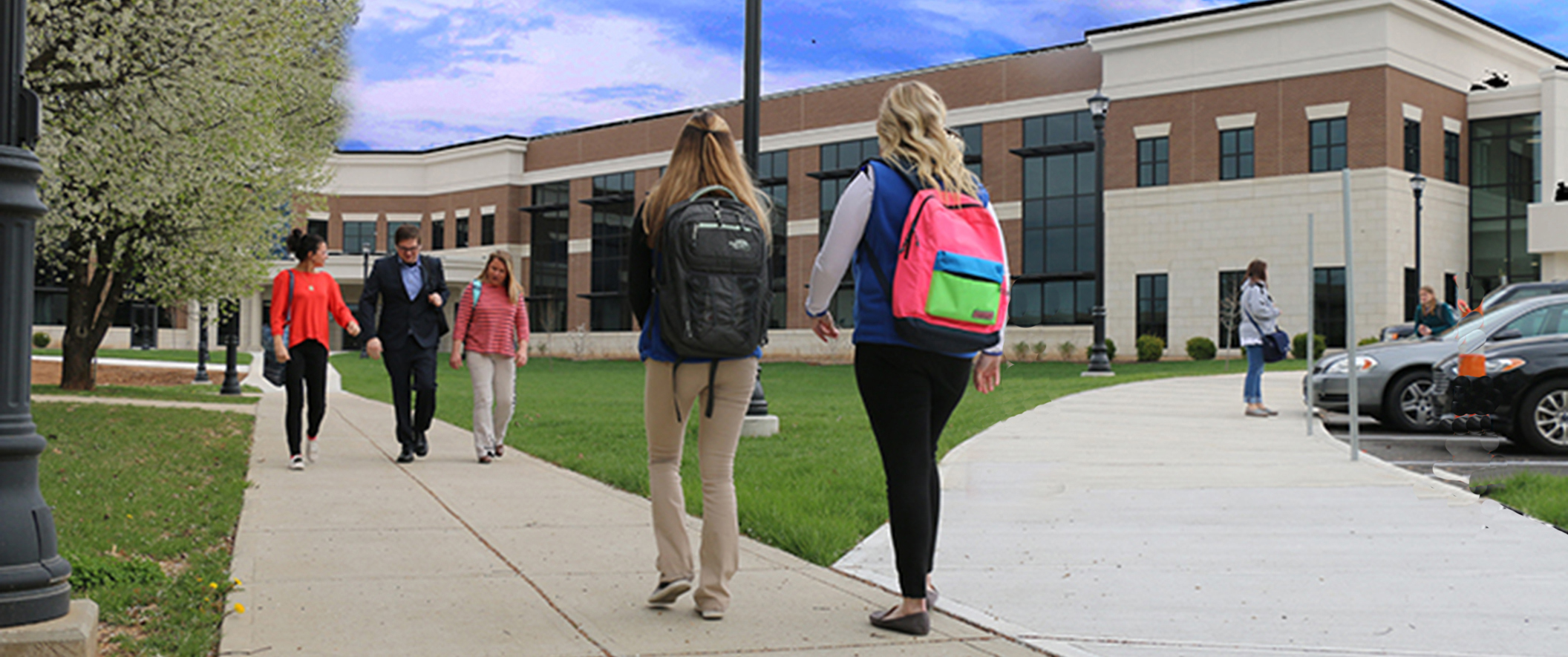 students with backpacks walking around campus on spring day