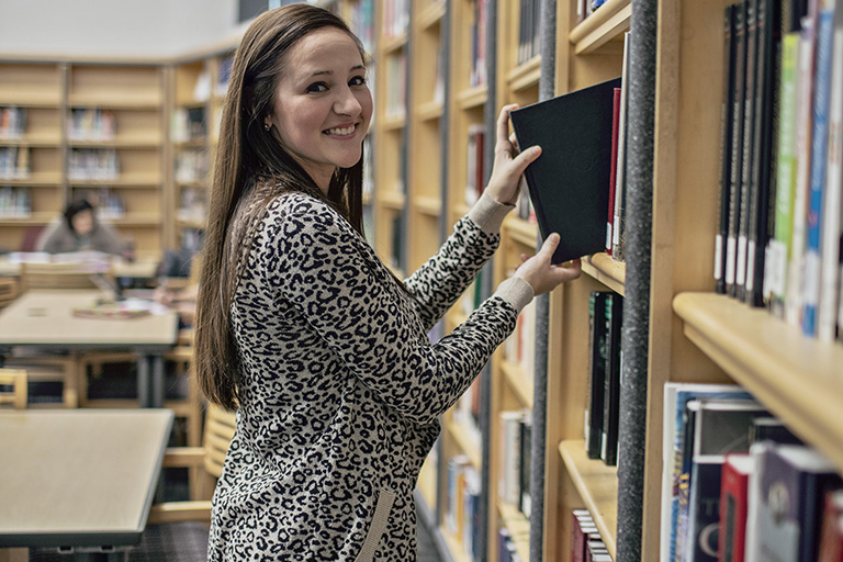 Woman taking book off of shelf
