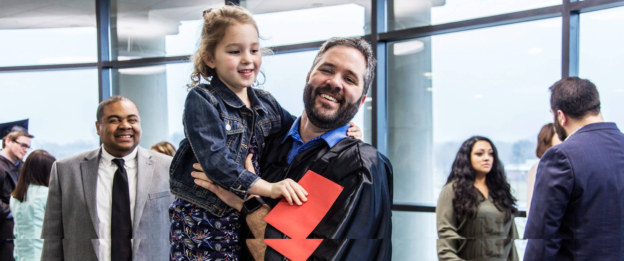 Graduate dad holds young daughter on graduation day