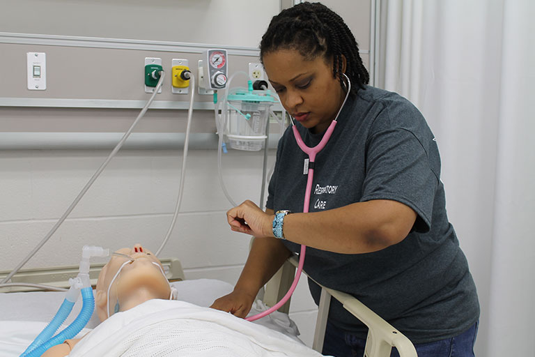 A nursing student checks for a pulse