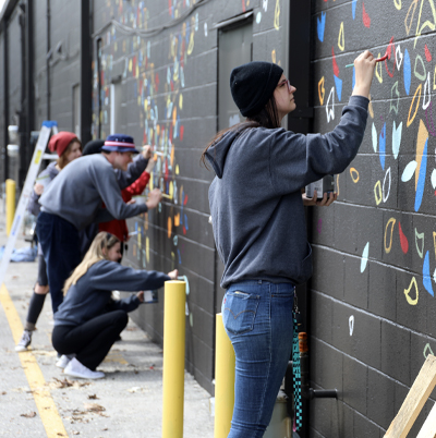 SKYCTC Art student paint mural on Thoroughbred Square wall
