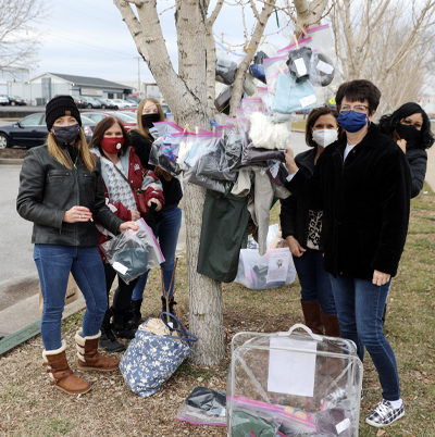 Phi Beta Lambda members of SKYCTC stand in front of the Warming Tree, decorated with clothes items for the homeless.