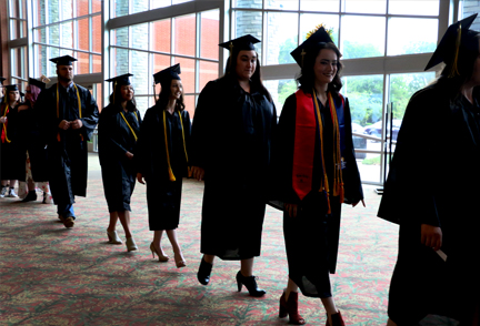 Graduates in cap and gown walking into the commencement ceremony