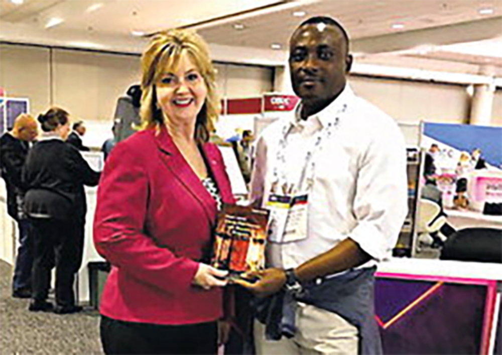 Paula Ratliff Pedigo stands with male pastor holding her book