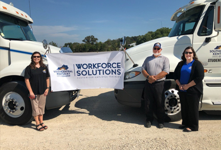 Three people standing in front of CDL trucks with banner saying Workforce Solutions
