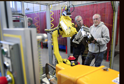Two men training on the FANUC robot
