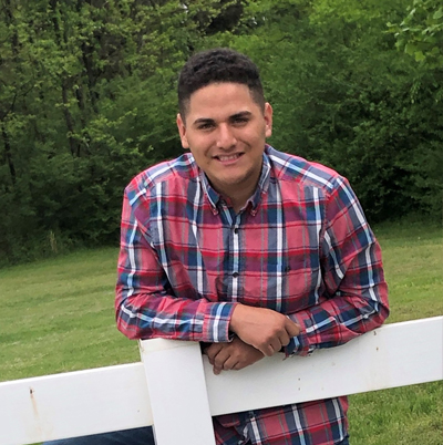 Picture of Rogelio Flores standing behind a fence outdoors