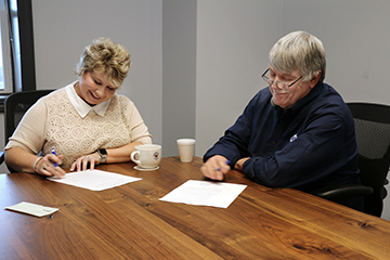 Mark and Christy Fuqua sign scholarship donatin papers