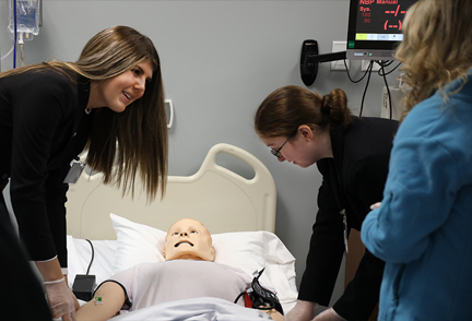 Three femal HOSA students checking vitals of manequin