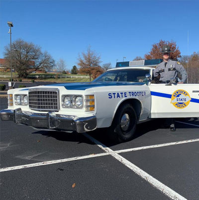State Trooper standing by state police Car refinished by SKYCTC Collision Repair Students